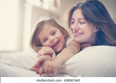 Mother with her cute little daughter lying on bed. 