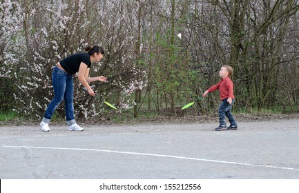 Mother and her cute young son playing badminton outdoors on asphalt in the park