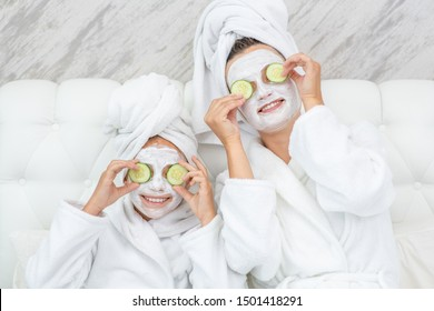 Mother and her daughter applying pieces of cucumber to their eyes like a glasses. Mom and child girl are in bathrobes and with towels on their heads