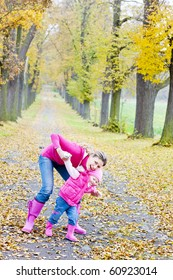 mother with her daughter in autumnal alley
