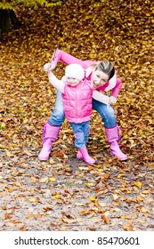 mother with her daughter in autumnal nature