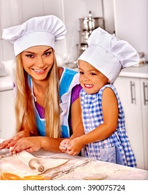 Mother and her daughter baking cookies on table kitchen. Mother learn kid cook at home kitchen.
