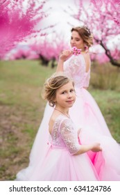 Mother with her daughter in blossom peach garden