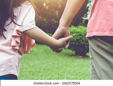 Mutter und ihre Tochter fangen sich im Garten die Hand. im Freien am Sommertag mit hellem Sonnenlicht. Fröhliche Familie verbringt Zeit zusammen im Urlaub. Filtereffekt von Vintage-Filmen.