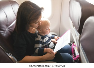 Mother and her daughter  checking safety  in economy class airliner