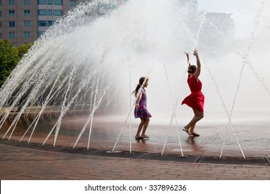 Mother and her daughter are dancing into the fountain.