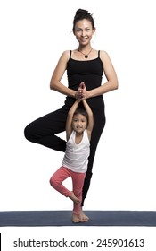 Mother and her daughter doing yoga exercise on studio white background.
