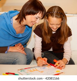 Mother and her daughter drawing together.