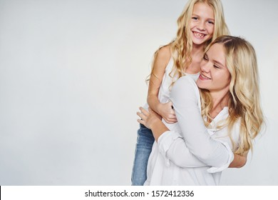 Mother with her daughter have fun together in the studio with white background.