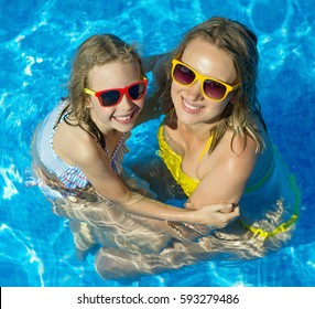 Mother and her daughter having fun in swimming pool.
