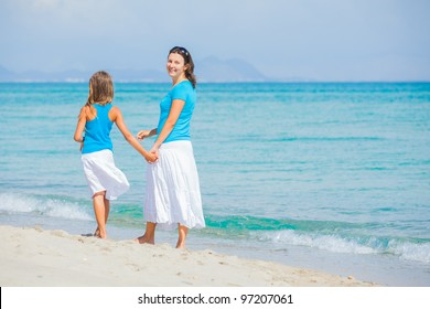 Mother and her daughter having fun on tropical beach