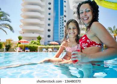 Mother and her daughter hide under umbrella from sun in pool