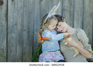 Mother and her daughter holding adorable little Easter rabbit