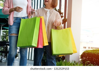 Mother with her daughter holding shopping bags in department store, happy family and people concept.