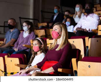 mother and her daughter in maskas sitting at perfomance in theatrical auditorium