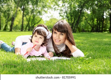 Mother with her daughter outside in the summer park
