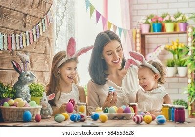 A mother and her daughter are painting eggs. Happy family are preparing for Easter. Cute little child girl wearing bunny ears.