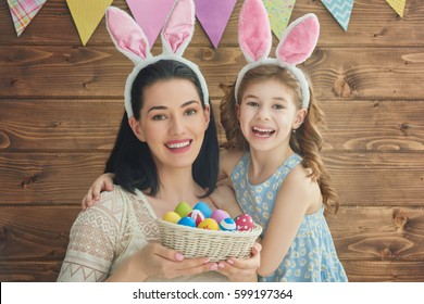 Mother and her daughter with painting eggs. Happy family celebrate Easter. Cute little child girl wearing bunny ears.