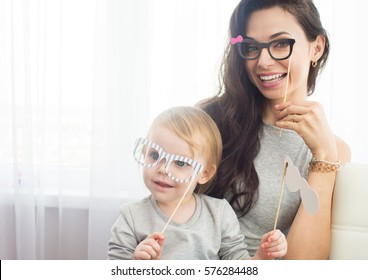 Mother and her daughter with a paper accessories.