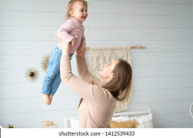 Mother and her daughter playing and laughing in their bedroom. Daughter in the arms of my mother. White bed linen, knitted blanket, macrame on the wall, hanging swing. Scandinavian style, cozy home.