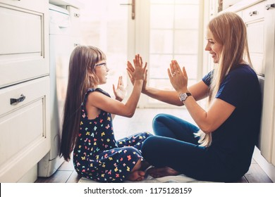 Mother with her daughter playing on the floor at the kitchen at home. Happy lifestyle family moments.