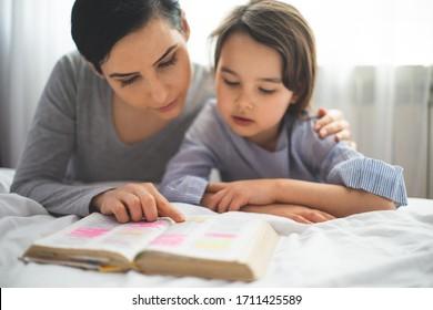 Madre y su hija leyendo de la biblia y rezando en sus rodillas cerca de la cama