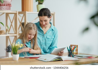 Mother and her daughter are smiling while spending time together. A day with family. Young pretty girl and her mom are studying with tablet. Education, studying and knowledge sharing concept.