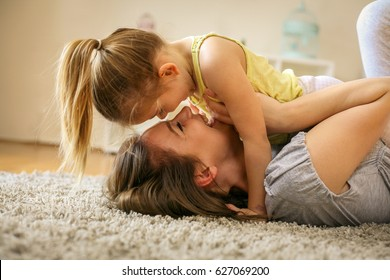 Mother with her daughter spending time at home. Mother lying on floor and sharing tenderness  little daughter.