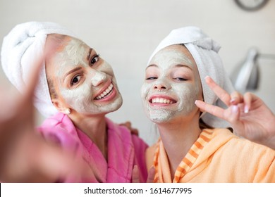 Mother and her daughter taking selfie by phone with facial mask and towel on head