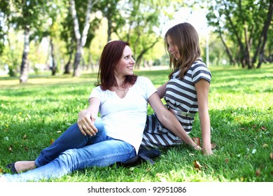 Mother with her daughter together in green summer park