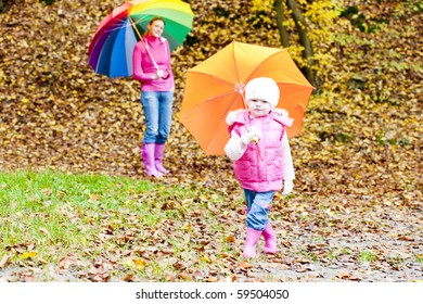 mother and her daughter with umbrellas in autumnal nature