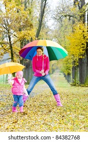 mother and her daughter with umbrellas in autumnal alley
