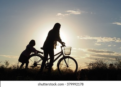 A mother and her daughter walk along a country road with a bicycle to back their home in the evening of winter: silhouette photo