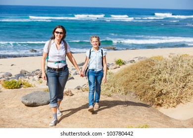 Mother with her daughter walking on a beach, wearing jeans and white shirts
