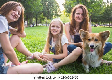 mother with her daughters and dog are sitting on a grass at the park