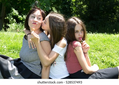 Mother with her daughters have fun on the grass