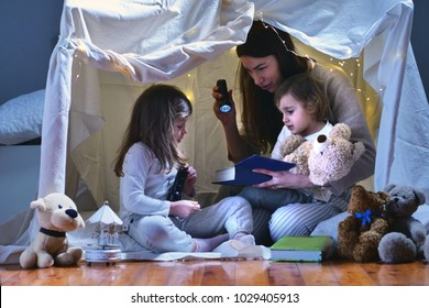 A mother with her daughters plays in the bedroom to read fairy tales in a tent built with sheets. Concept of: family, protection, educational, magic, creativity.