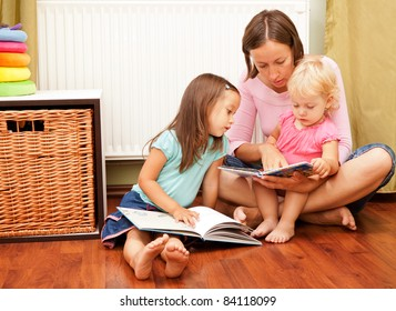 mother and her daughters reading a book on the floor