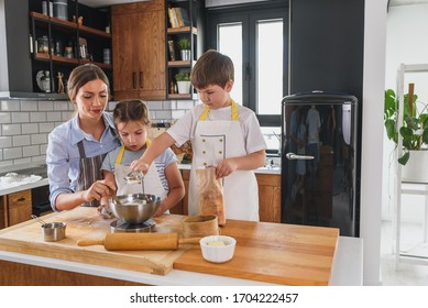 Mother and her kids making apple pie in the kitchen. Teaching children to help at home