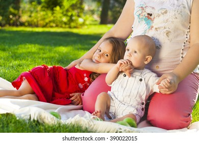 Mother And her kids outdoors. Happy mum and her children playing in park together. Outdoor portrait of happy family
