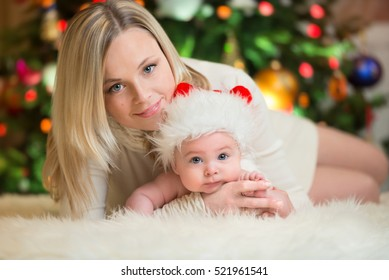 Mother with her little baby in red cap of Santa Claus celebrates Christmas. Christmas photo of infant in red cap. New Year's holidays and Christmas tree.