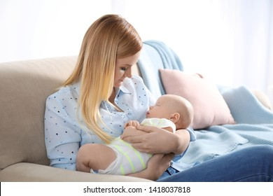 Mother with her little baby sitting in armchair at home