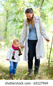 Mother and her little daughter at autumn forest
