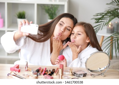 Mother and her little daughter in bathrobes taking selfie while applying makeup at home