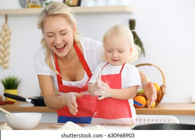Mother and her little daughter cooking holiday pie or cookies for Mother's day. Concept of happy family in the kitchen.