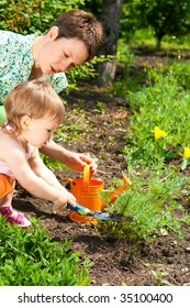 Mother and her little daughter doing gardening