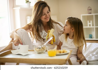 Mother with her little daughter having breakfast in the bed. Mother and her daughter enjoying a healthy breakfast together. Little girl eating banana.