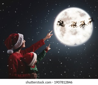 Mother and her little daughter looking at Santa Claus with reindeers in sky on full moon night. Christmas holiday