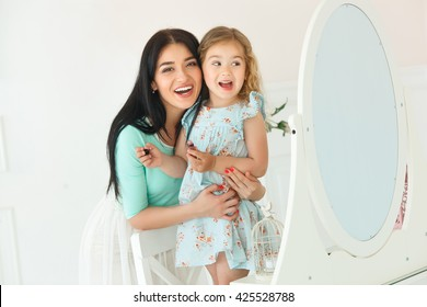 Mother and her little daughter making up each other and looking at the mirror. Smiling.