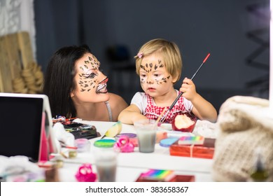 Mother and her little daughter painting their faces in front of the mirror